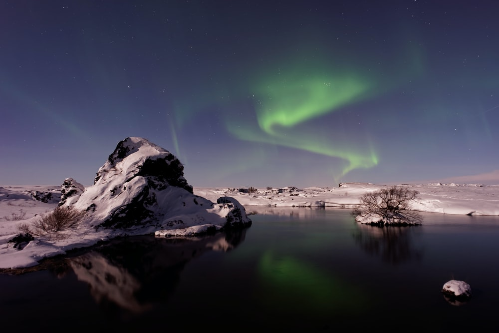 river beside snowfield under aurora borealis