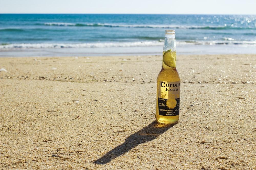 Corona Extra bottle on seashore during daytime