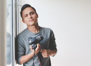 man holding DSLR camera leaning on windowpane