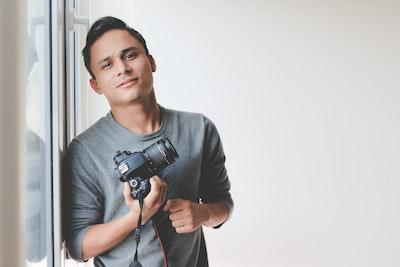 man holding dslr camera leaning on windowpane photographer zoom background