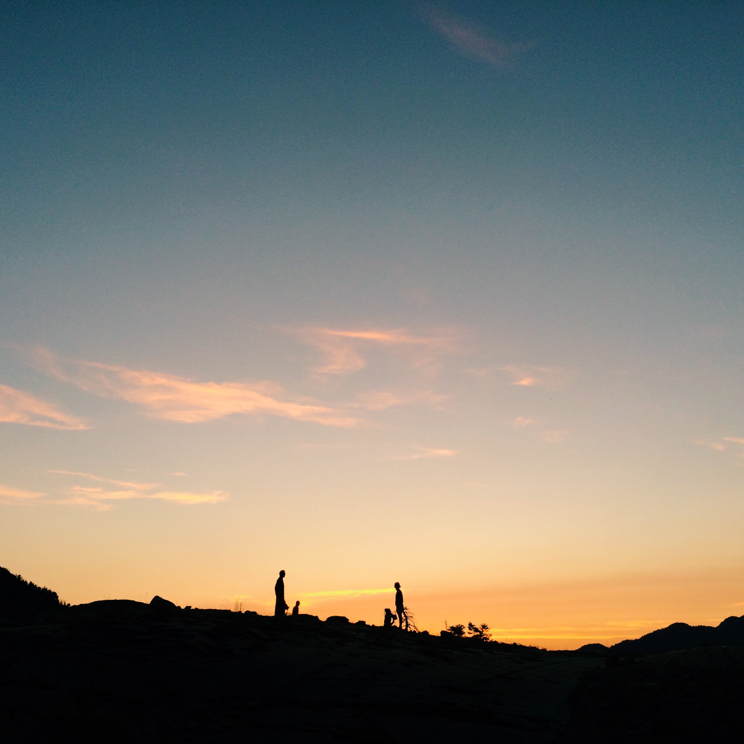 Two people in silhouette on a hill against a gold and blue sunset at Lake Blanche.
