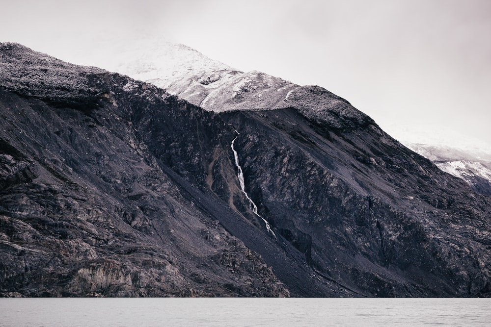 grayscale photo of body of water surrounded by mountain