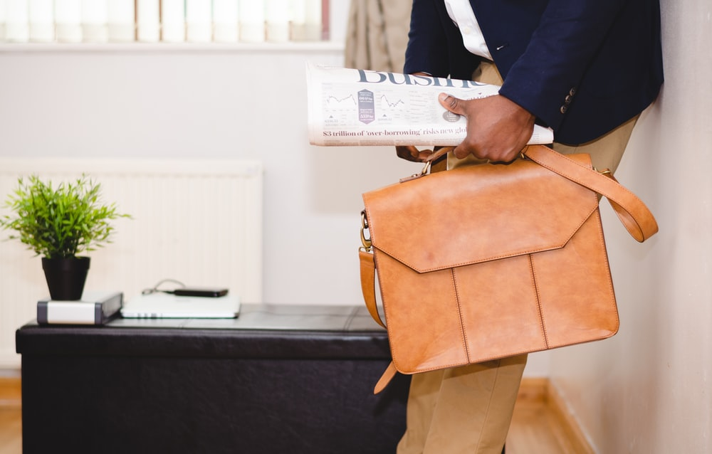 man holding brown leather bag leaning on white wall