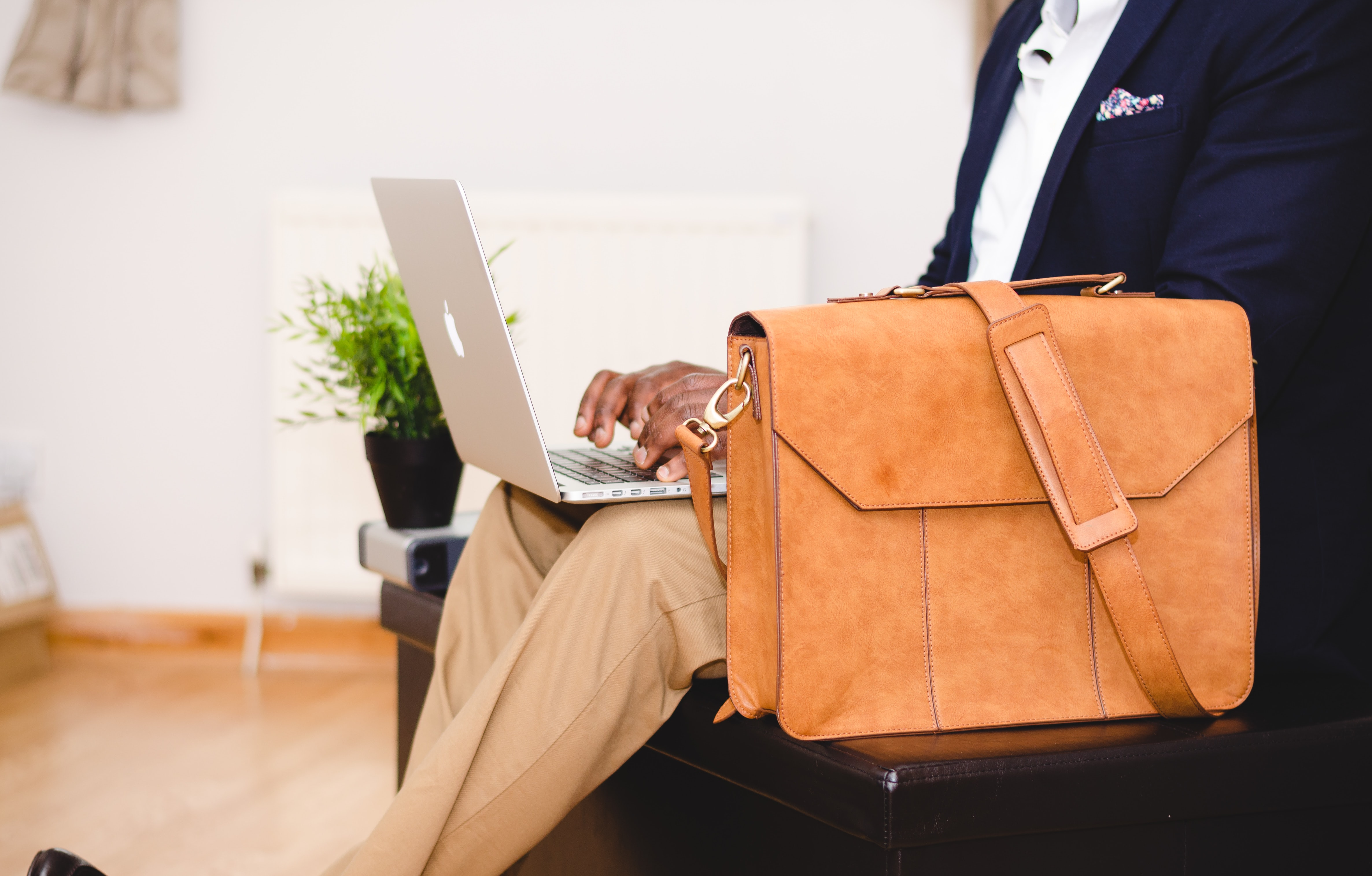 person using MacBook Pro beside brown leather briefcase