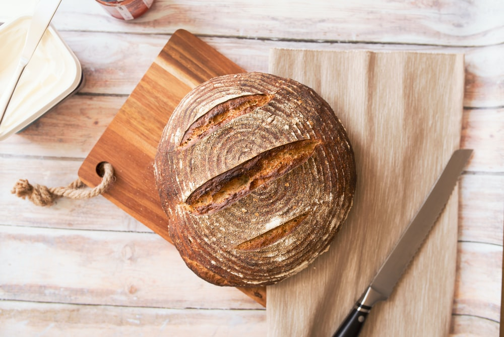 closeup photo of baked bread on chopping board