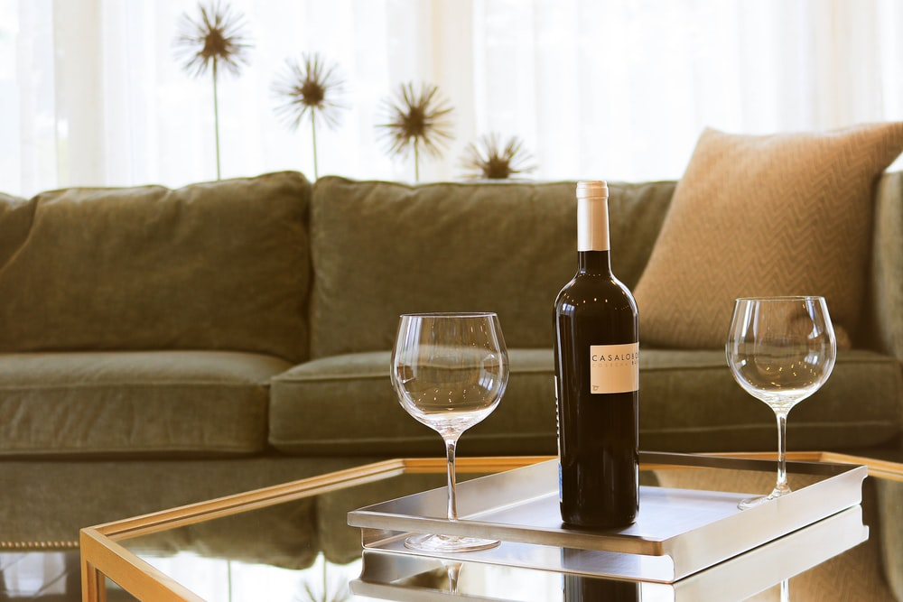 black wine bottle beside two wine glasses