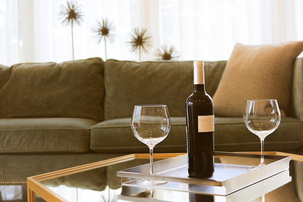 black wine bottle beside two wine glasses