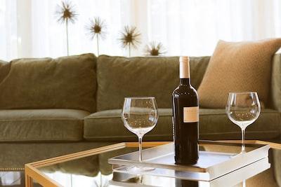 black wine bottle beside two wine glasses honduras zoom background