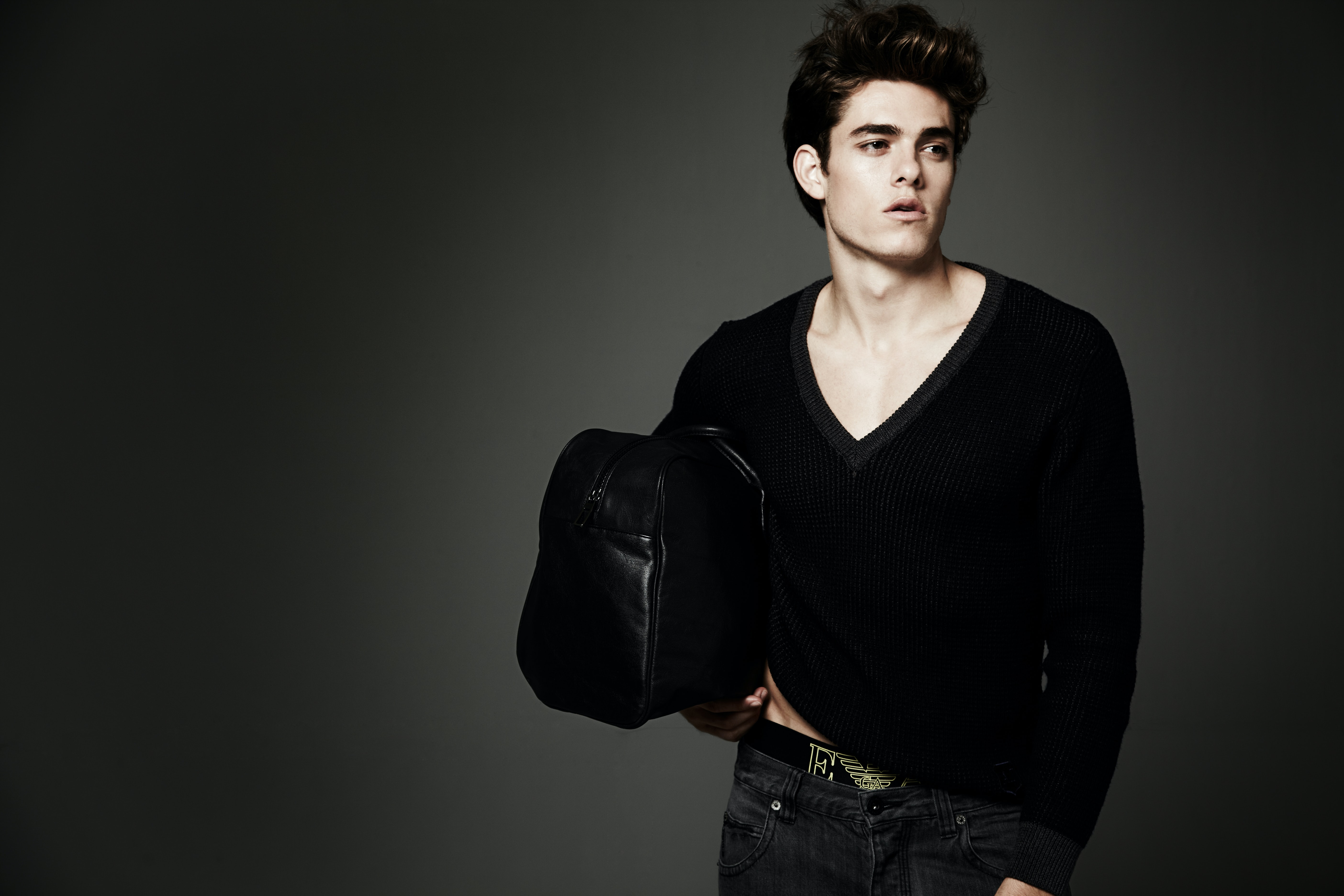 man holding leather bag posing for a photo shoot
