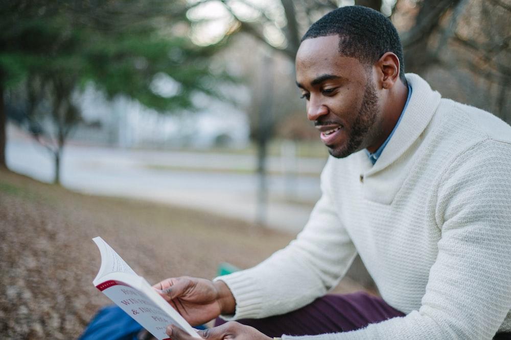 man wearing white sweater while reading book