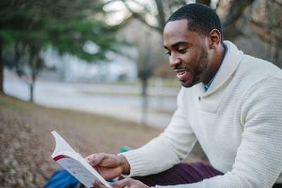 man wearing white sweater while reading book read teams background