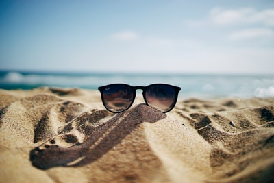 black ray-ban wayfarer sunglasses on beach sand summer teams background