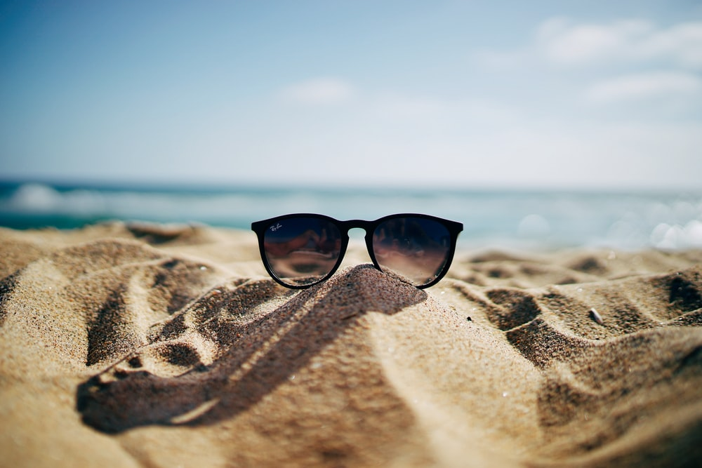 black Ray-Ban Wayfarer sunglasses on beach sand