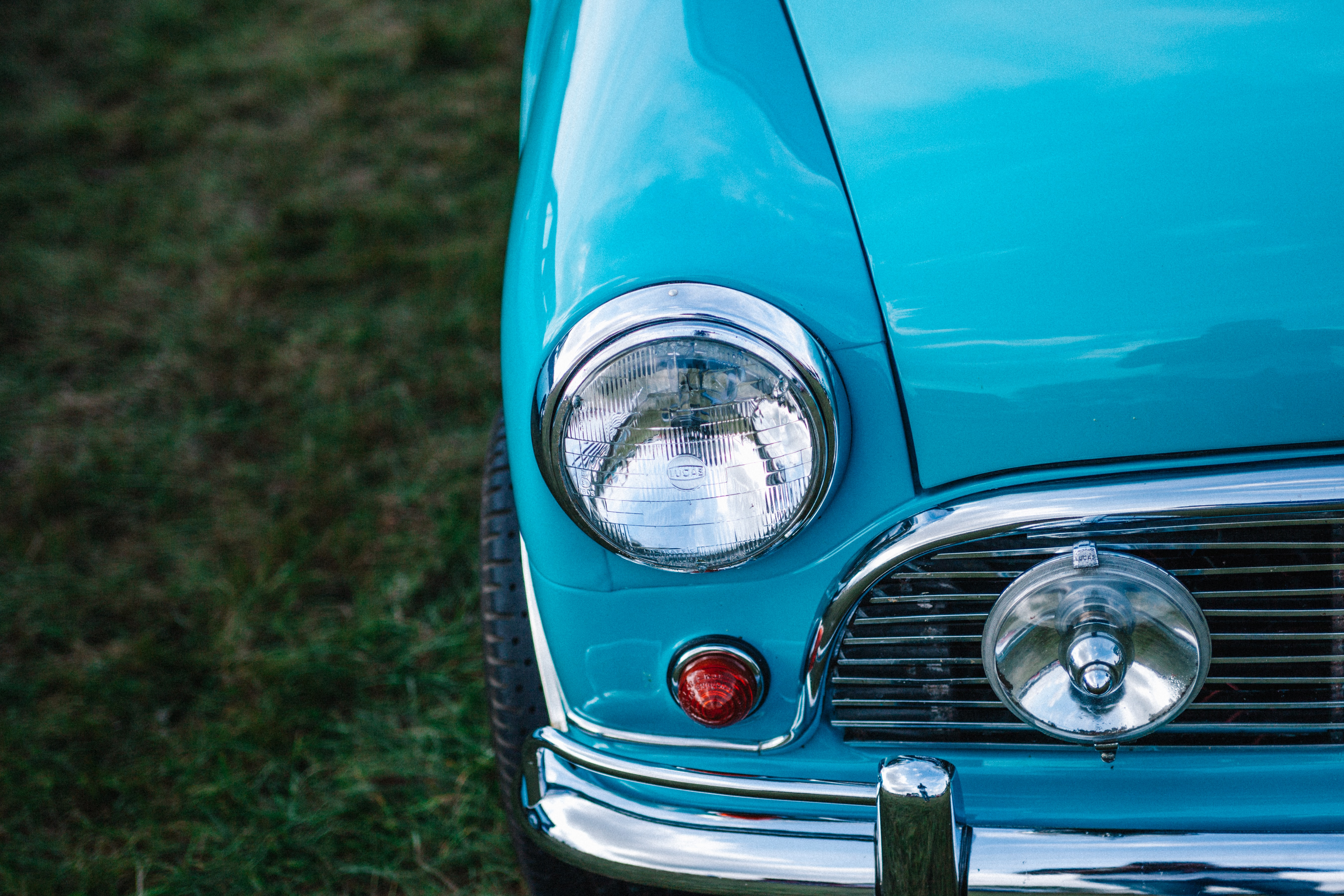 Headlight and hood details on a baby blue vintage car