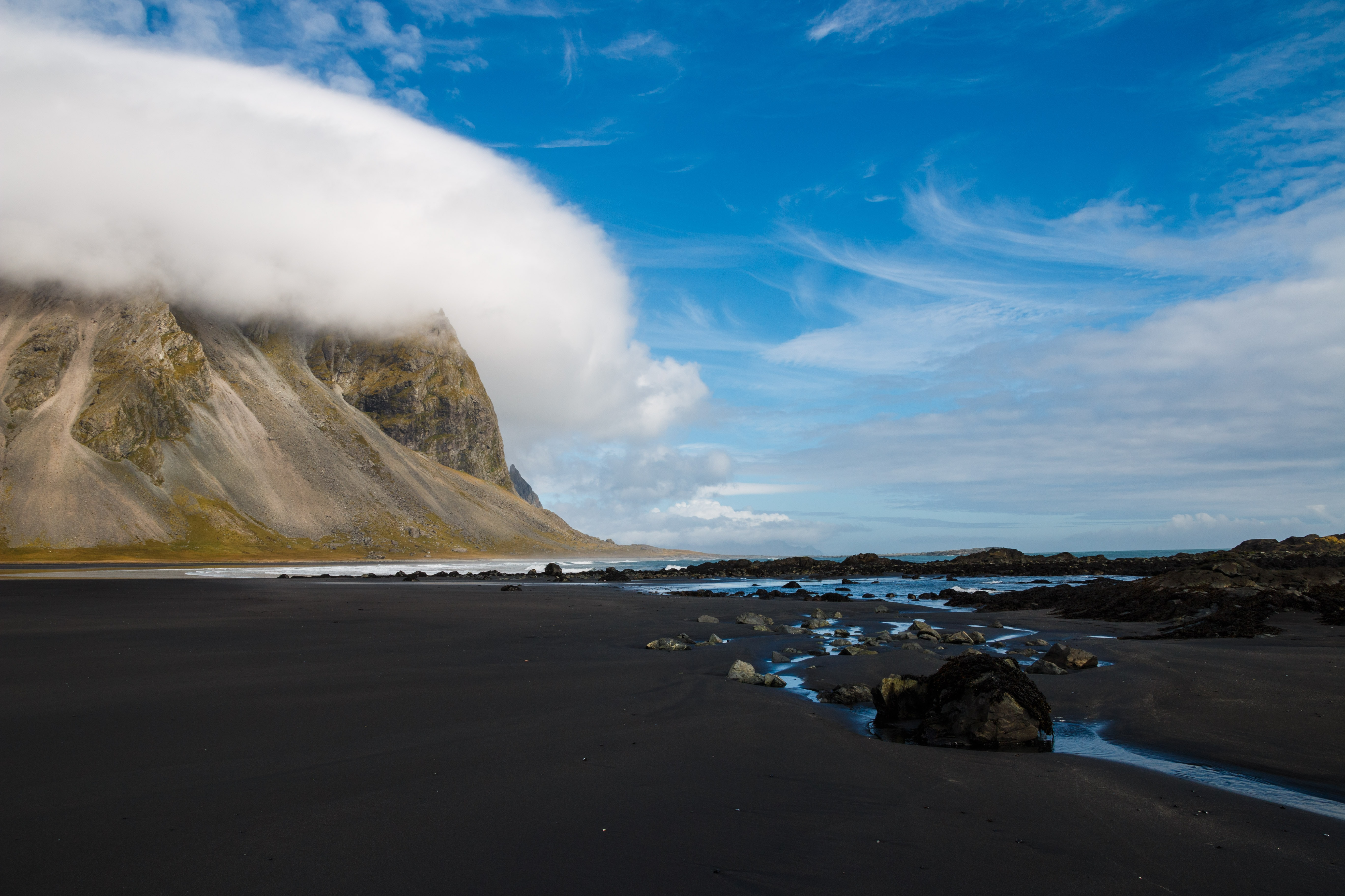 Cold, rocky shore near a mountain covered in clouds