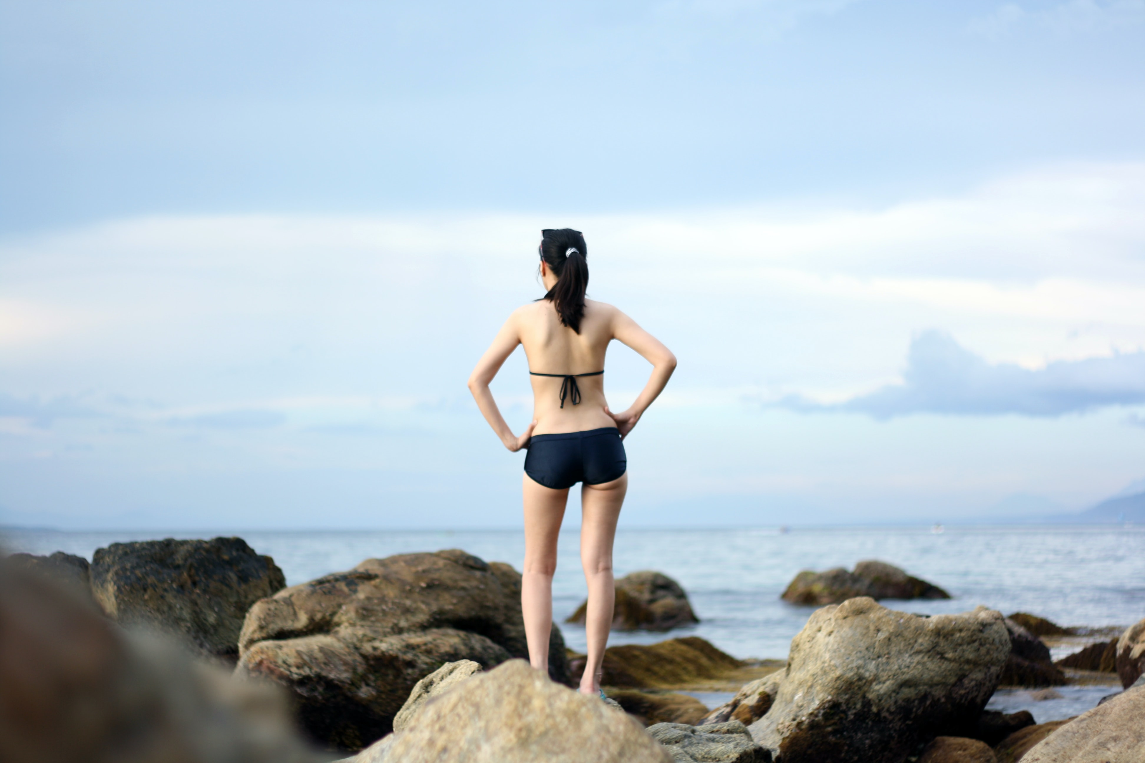 An attractive woman standing on large rocks looking out into the ocean