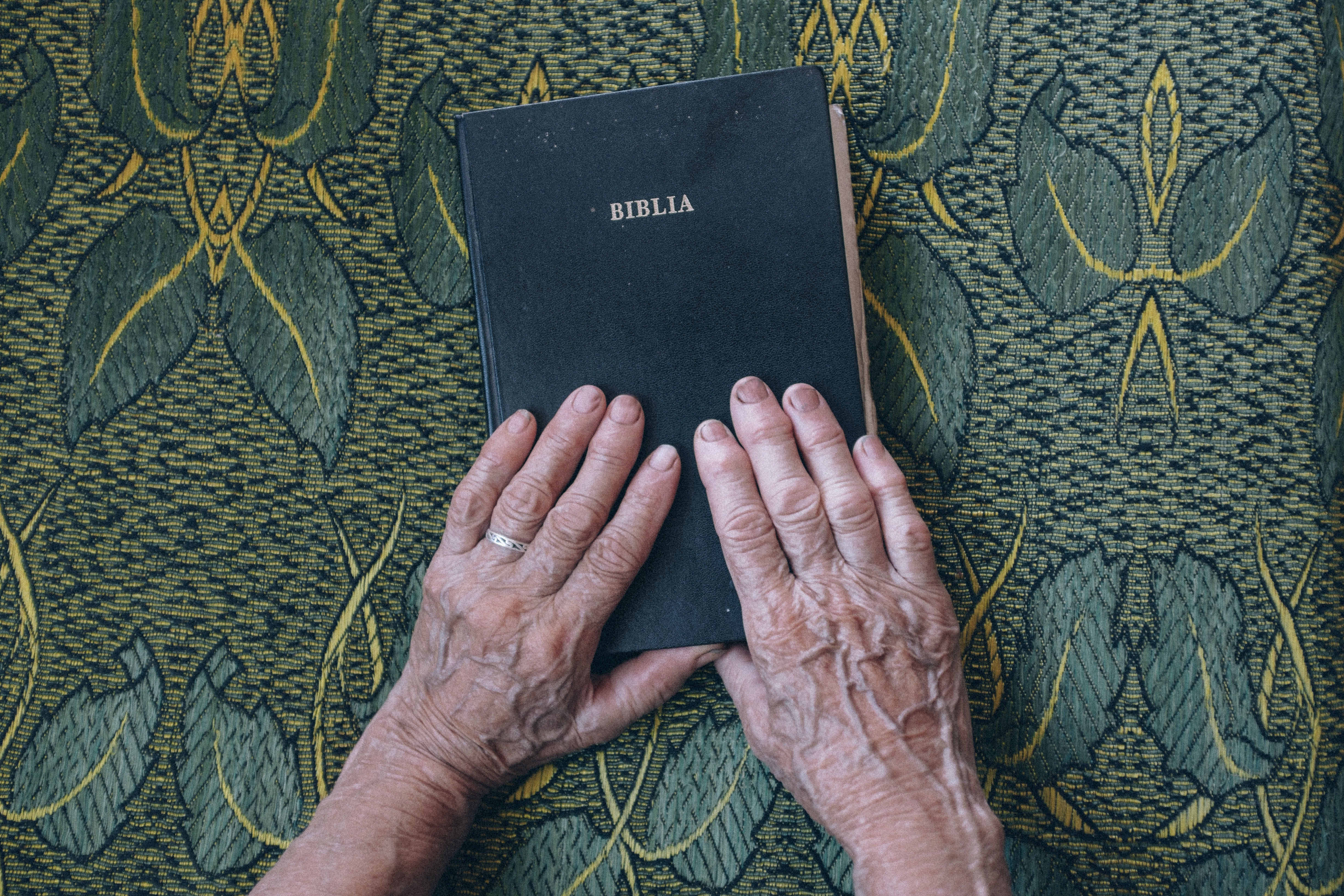 Two elderly hands touching a Romanian bible placed on a green leaf print.