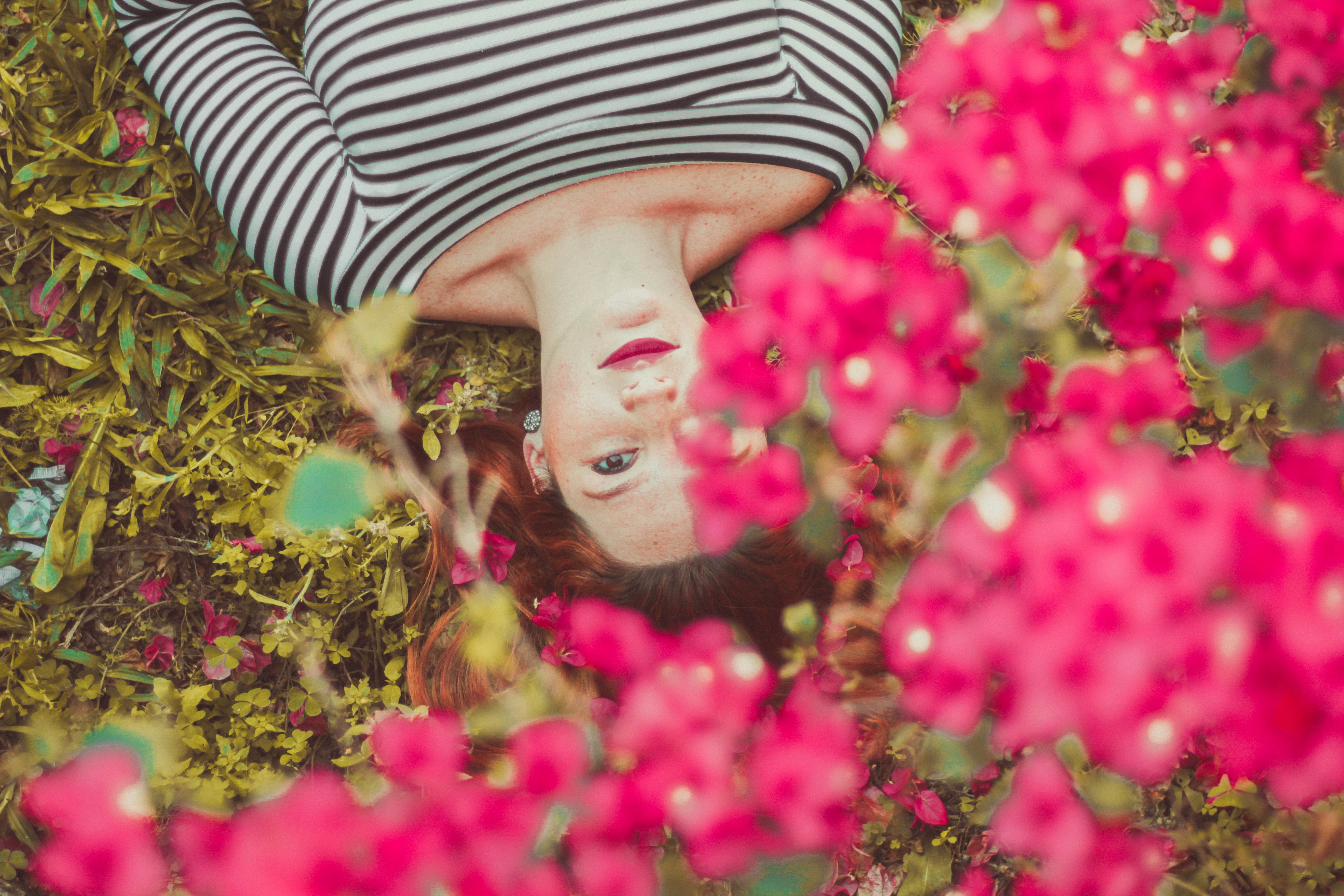 A woman lying on her back in the grass with pink flowers over her head