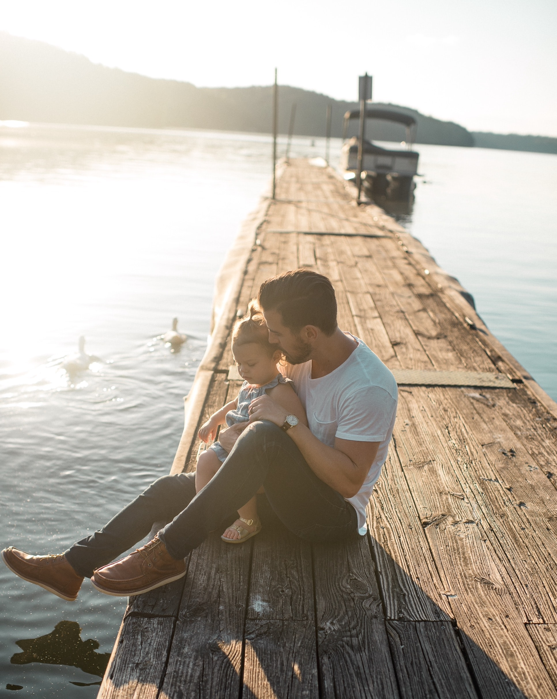 Father holding child on a wooden pier in bright sunlight as ducks swim by
