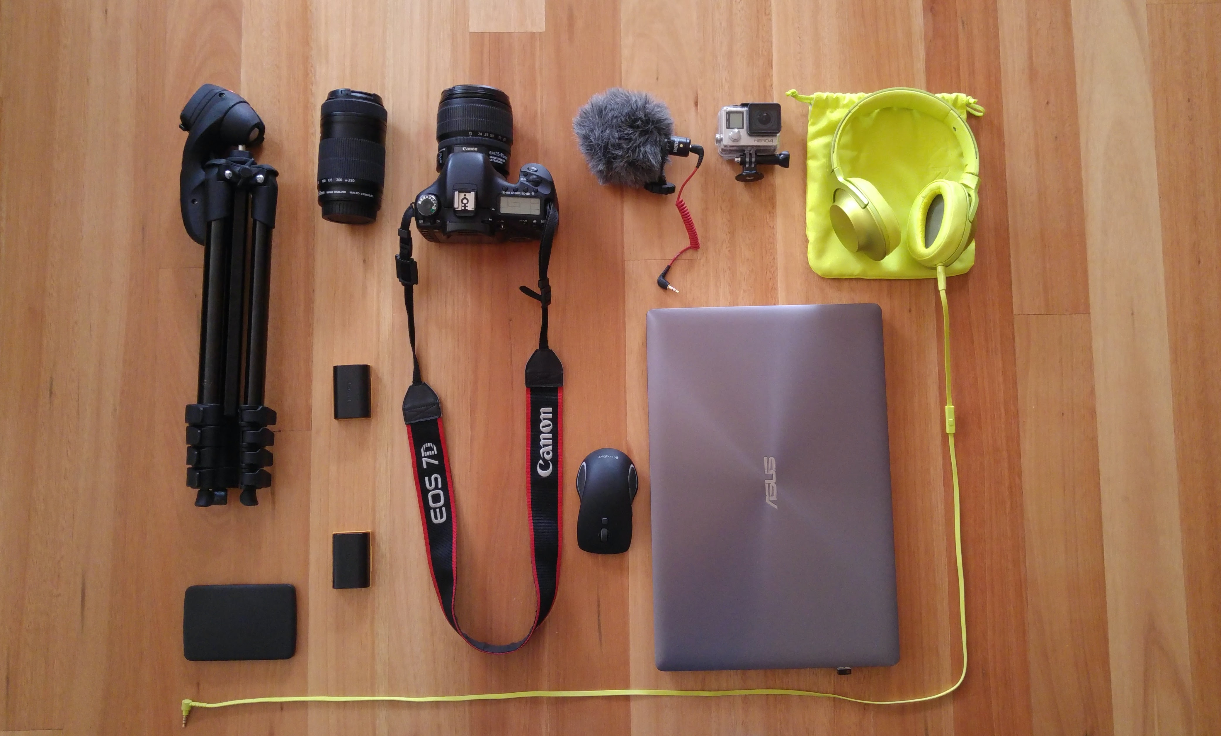 A flatlay image of photography equipment, headphones and a laptop on the floor.
