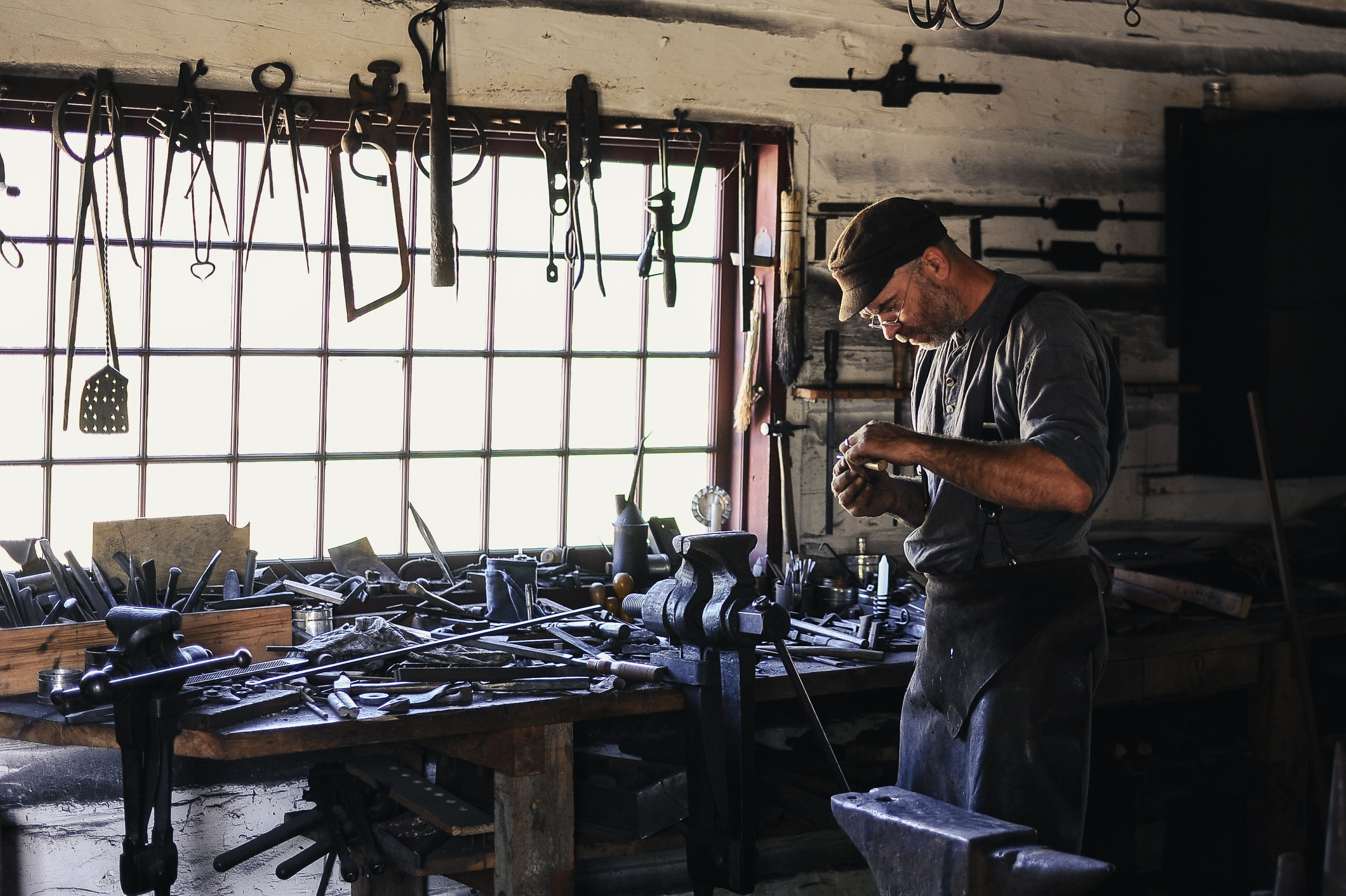 A middle-aged man working near a workbench with various tools on it in a workshop