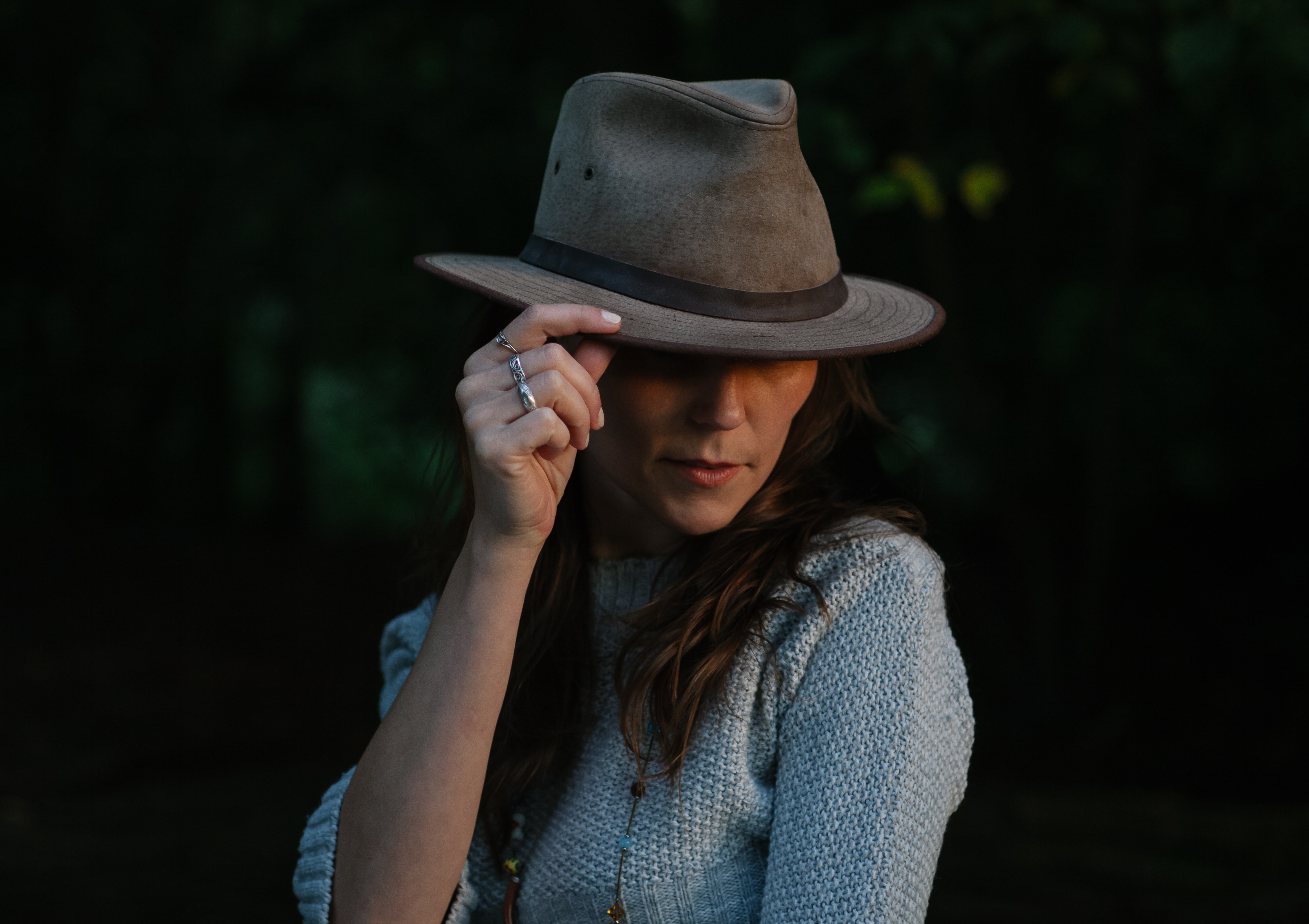 woman in blue sweater holding her hat