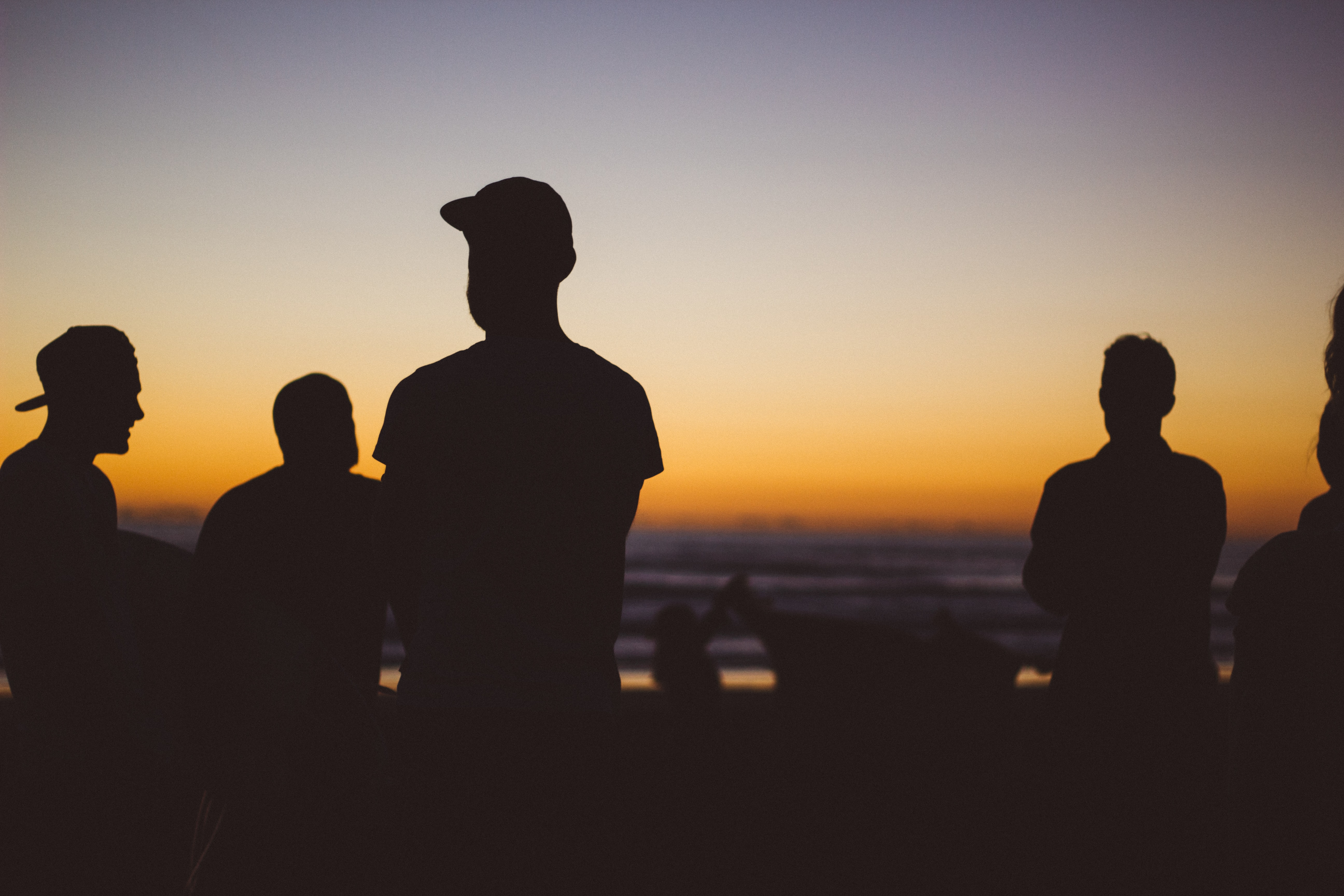 Silhouettes of a group of men standing on Piha Beach during sunset