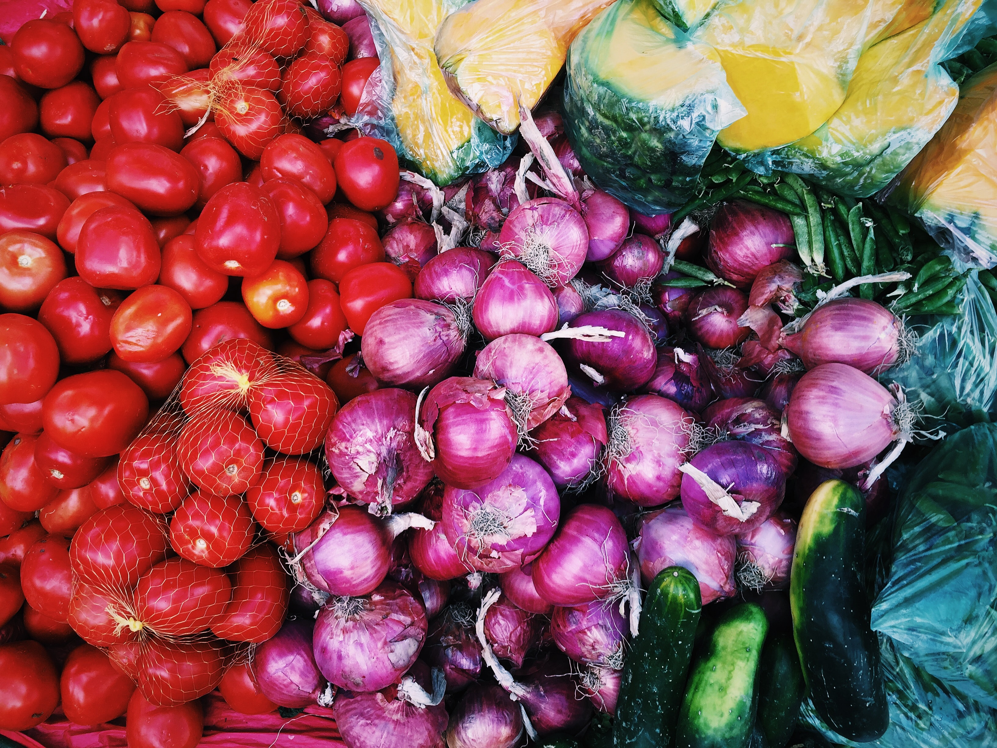 Colorful vegetables like tomatoes, onions, cucumbers, and squash at a market in Písac, Cuzco, Perú