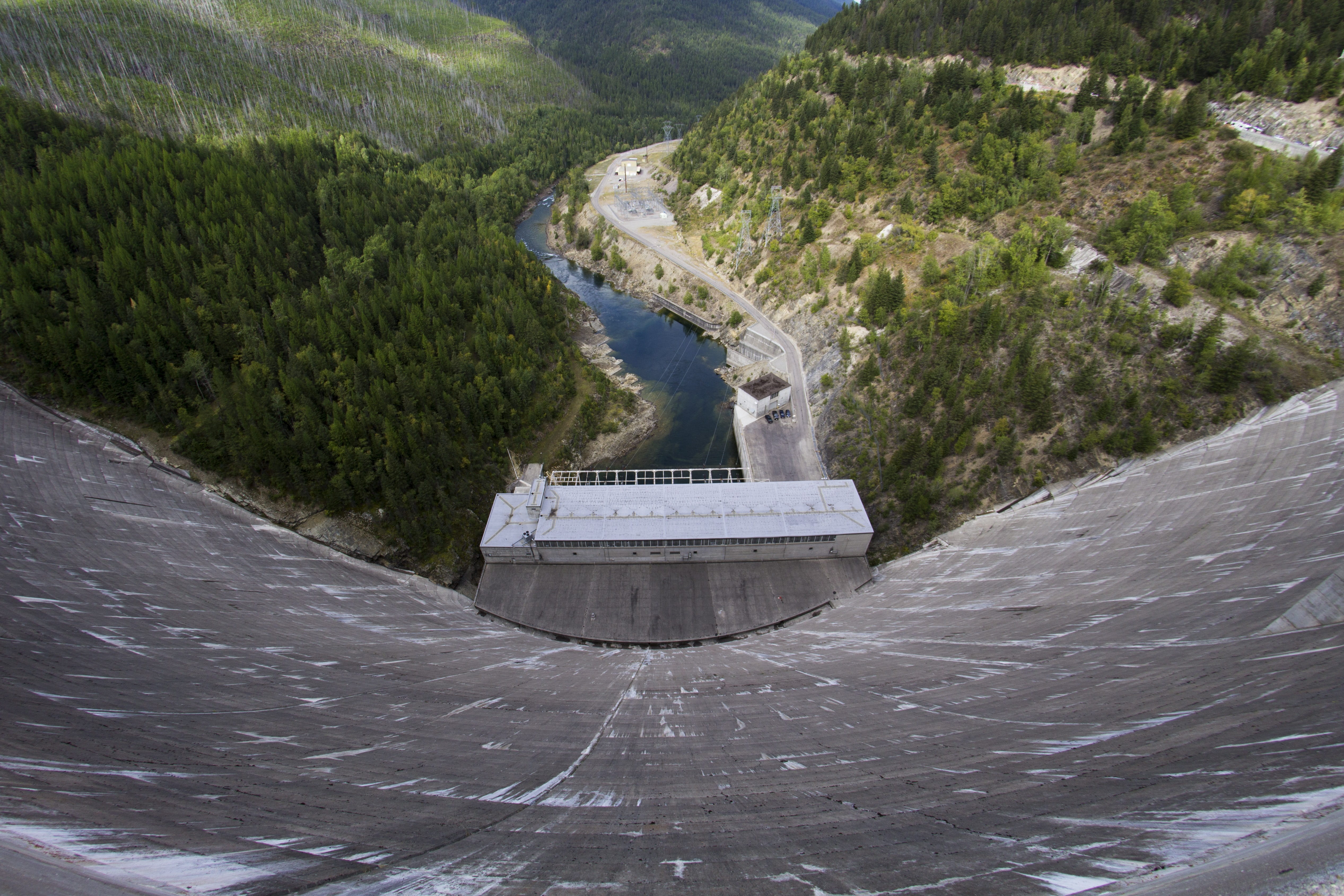 View from the top of a tall concrete dam on the river below