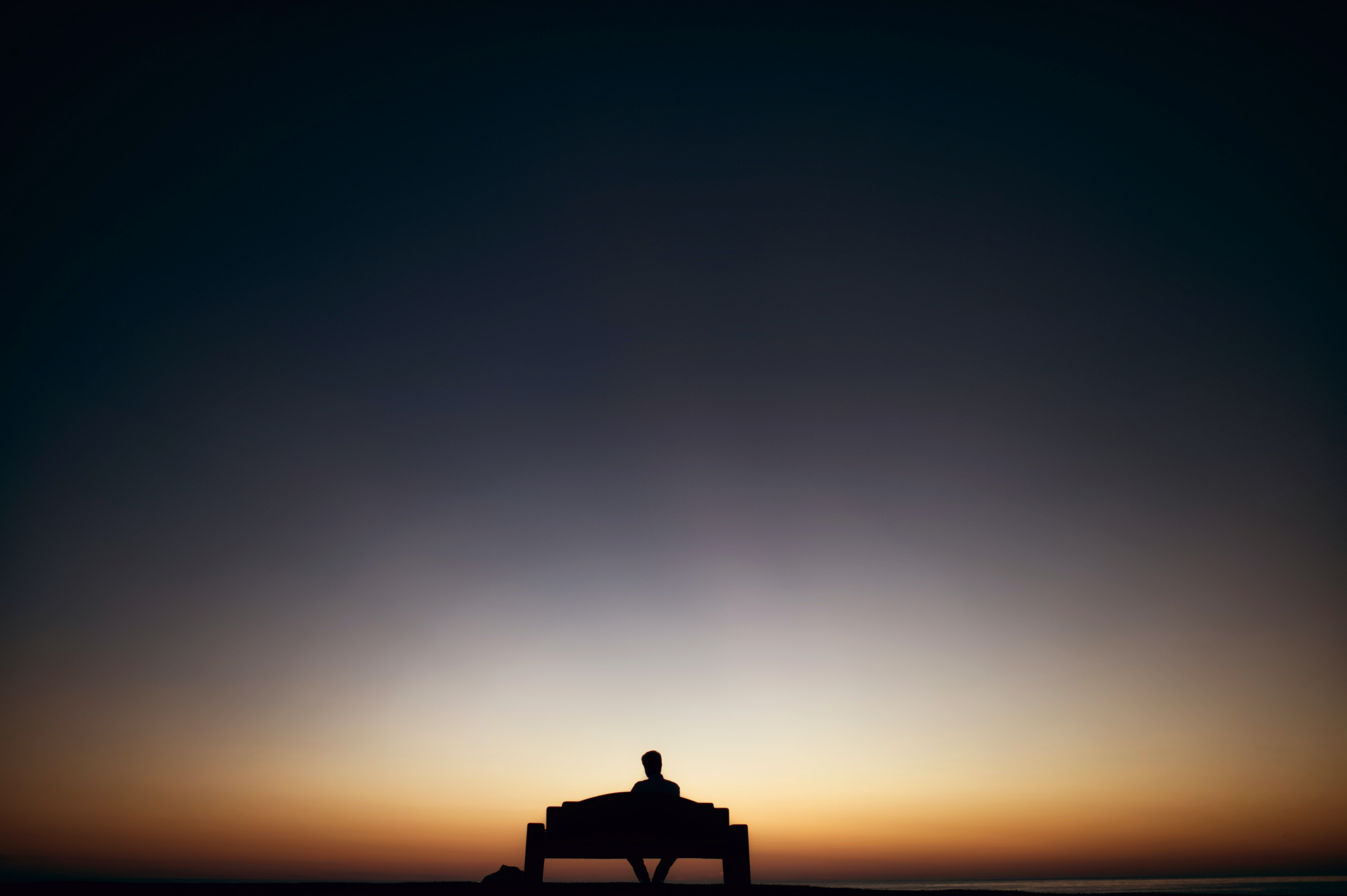 Sunset silhouette of a man sitting on bench alone in San Diego