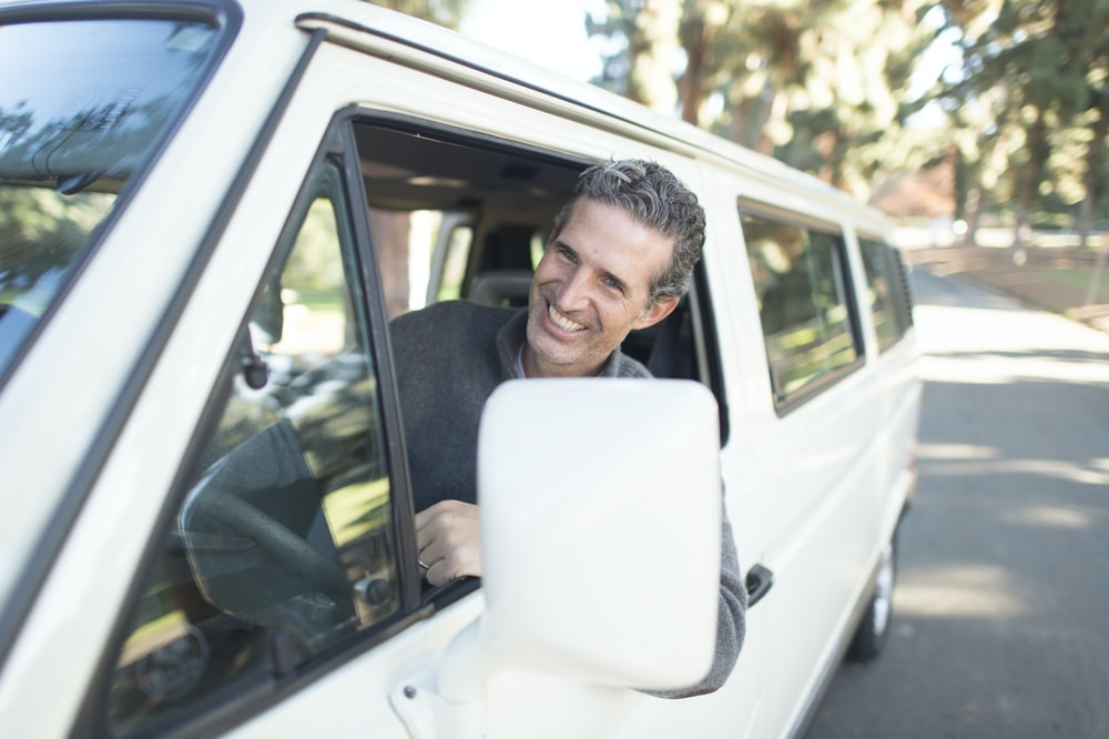 man in gray sweater leaning on van window
