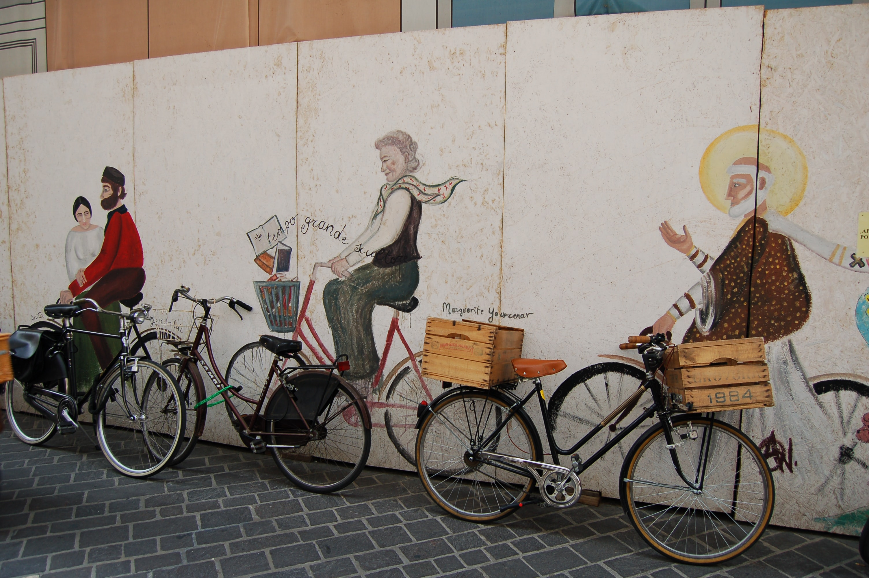 An illusion graffiti painting of people sitting on a wall, with real bikes lined up to look like they're riding them.