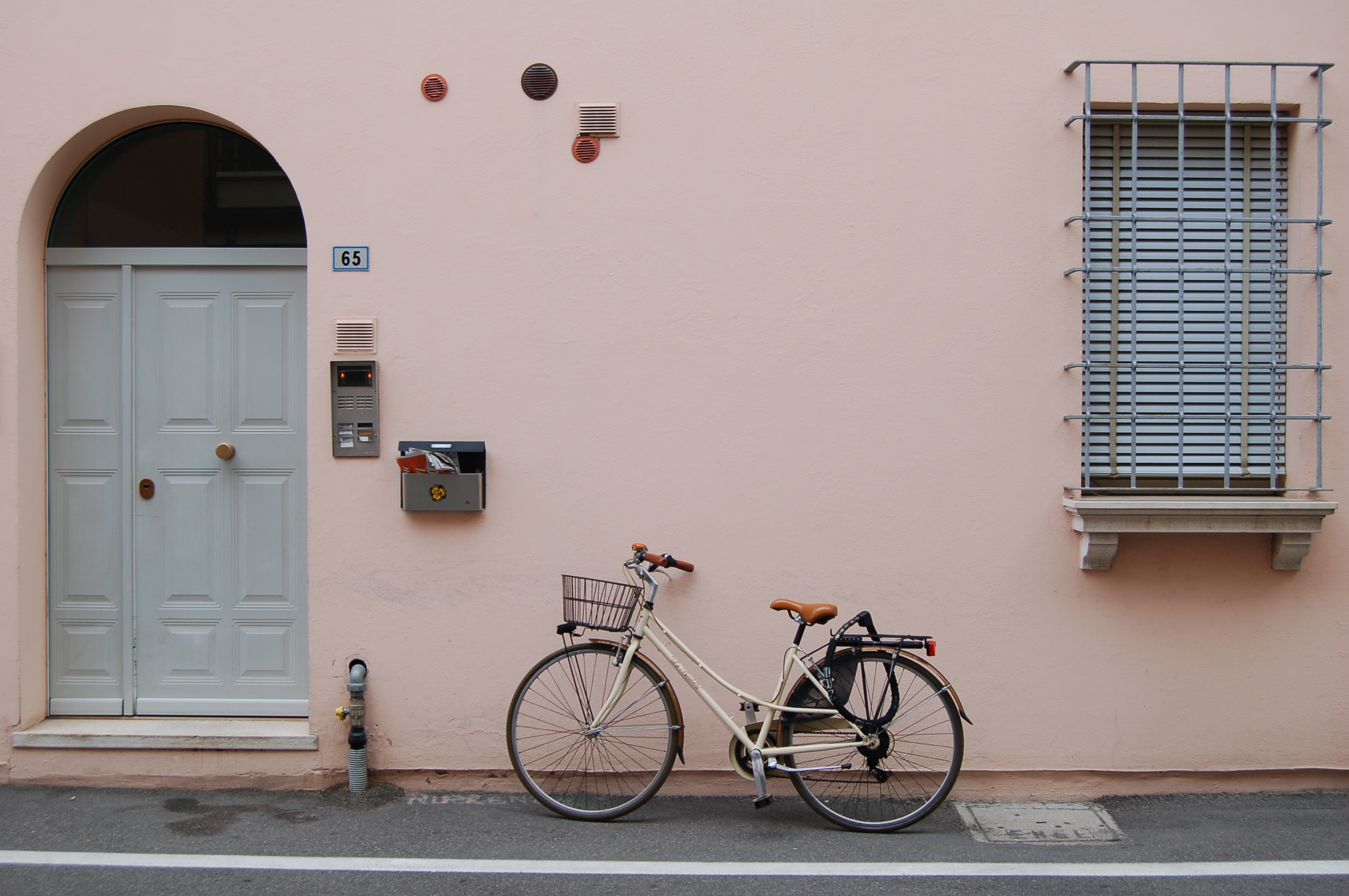 white commuter bike parked on pink painted wall building