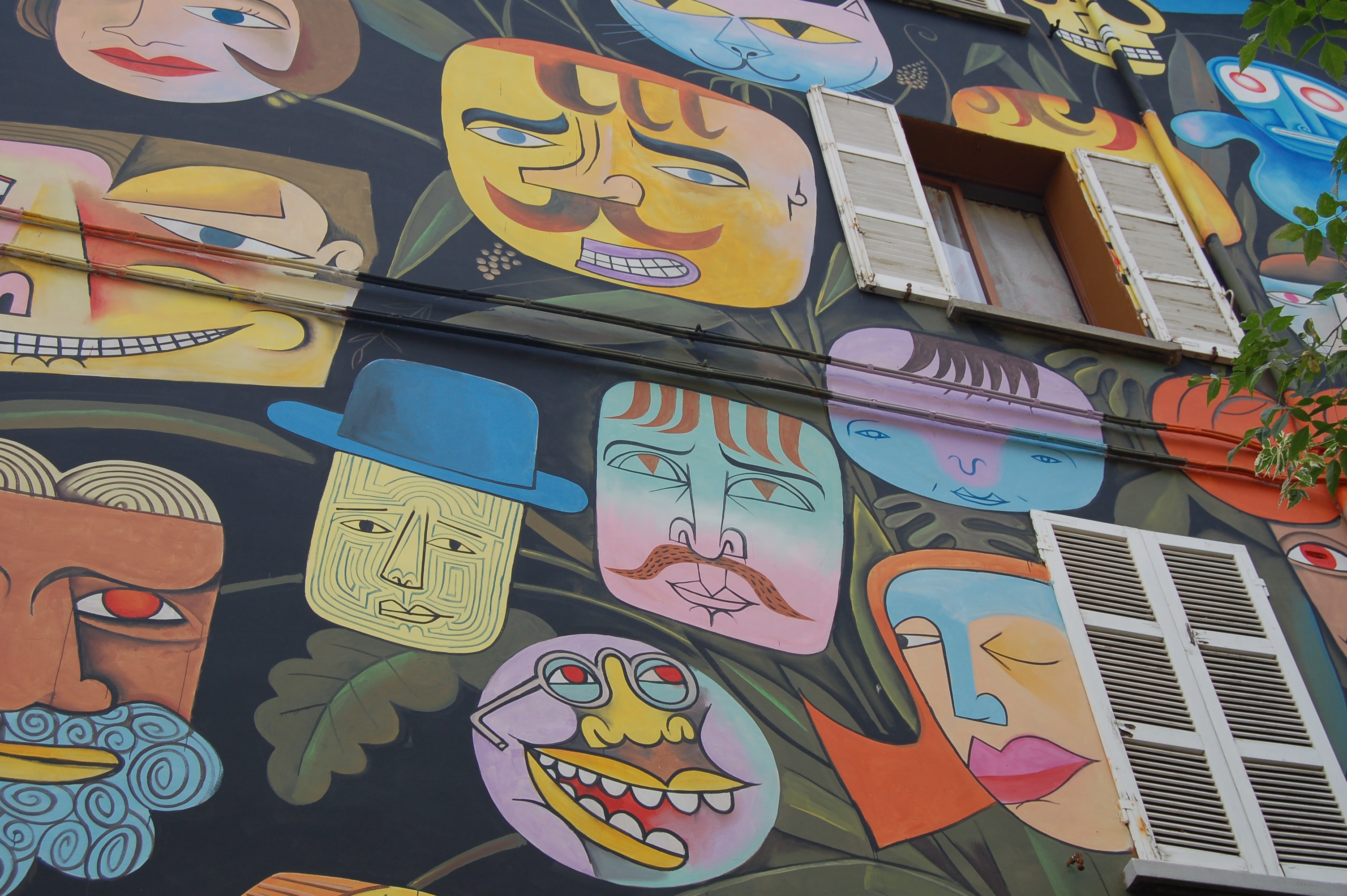 Many colorful faces painted on a building wall.