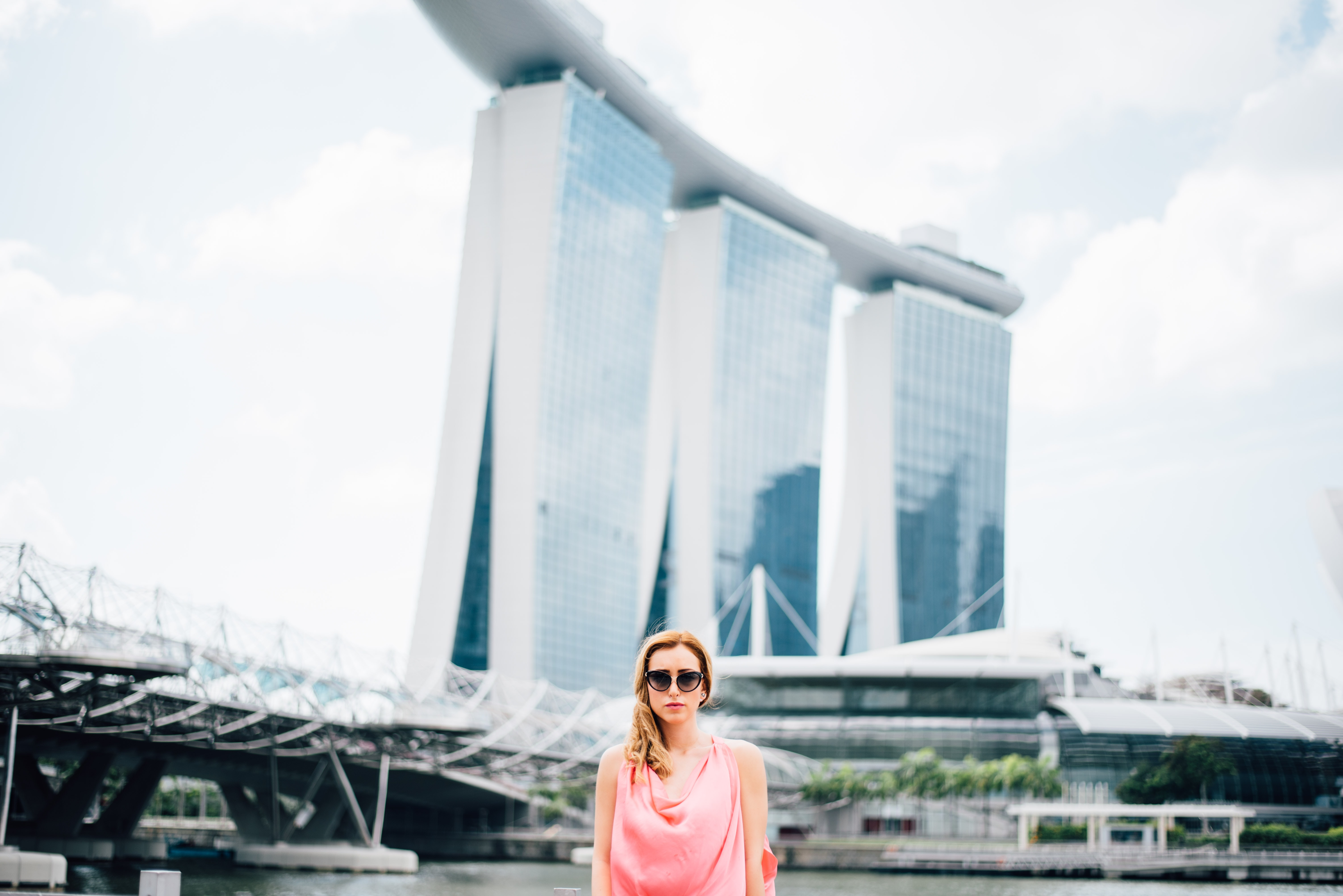 A girl wearing a pink dress and black sunglasses standing in front of Marina Bay Sands in Singapore
