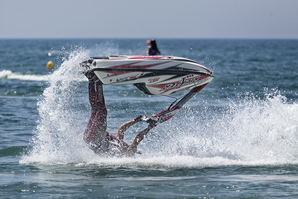 person riding personal watercraft doing acrobat on body of water during daytime