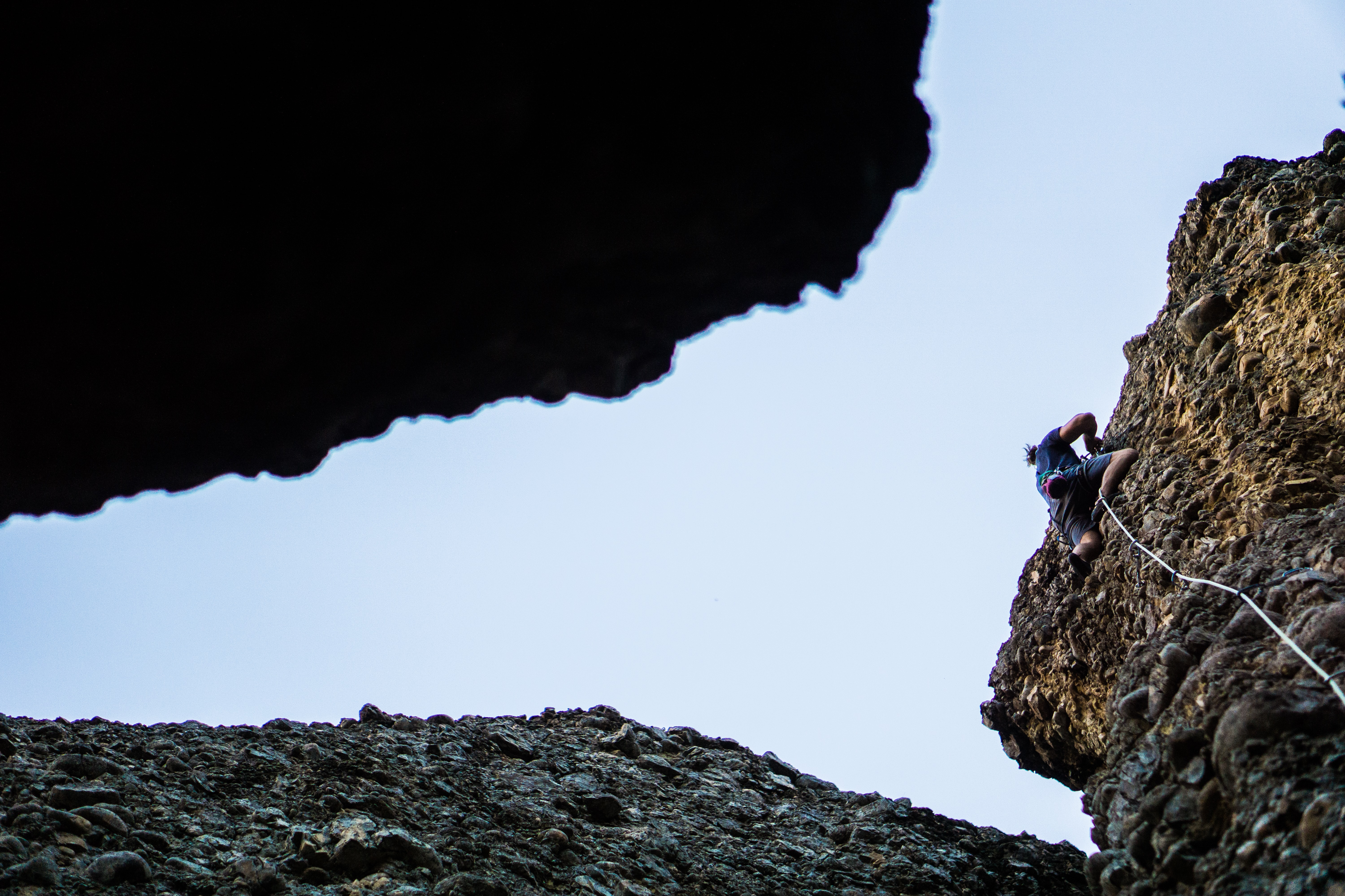 person on blue shirt and black shorts climbing cliff