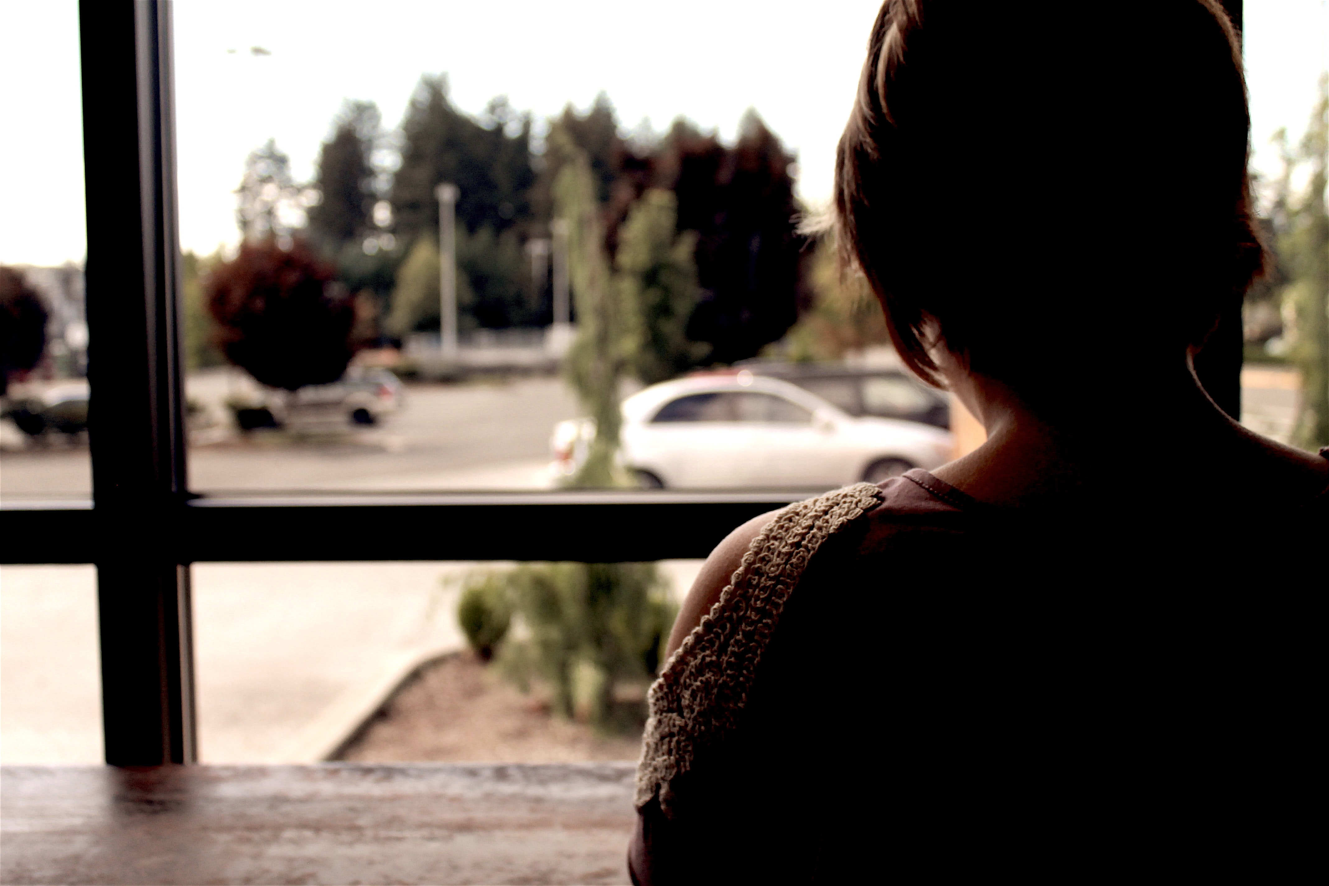 Person sitting at a cafe ledge looking out the window