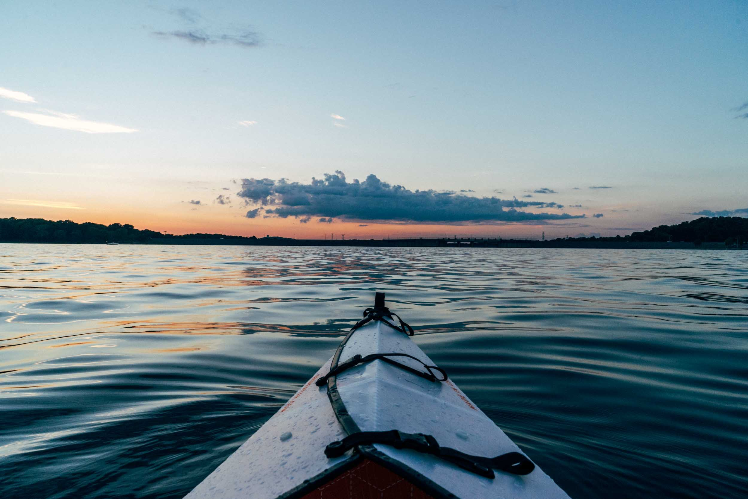 A perspective shot from a kayak on a rippling lake with the sun setting on the horizon in the distance