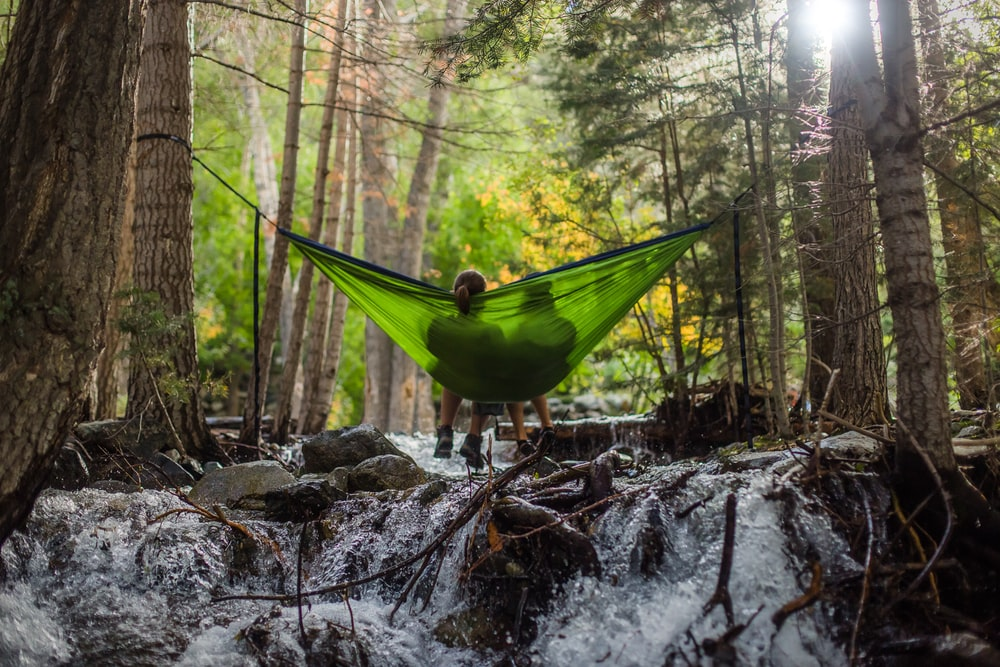 two person on green mesh hammock outdoor