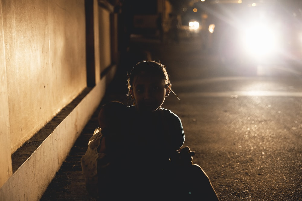 silhouette photography of girl sitting on pavement while carrying a baby