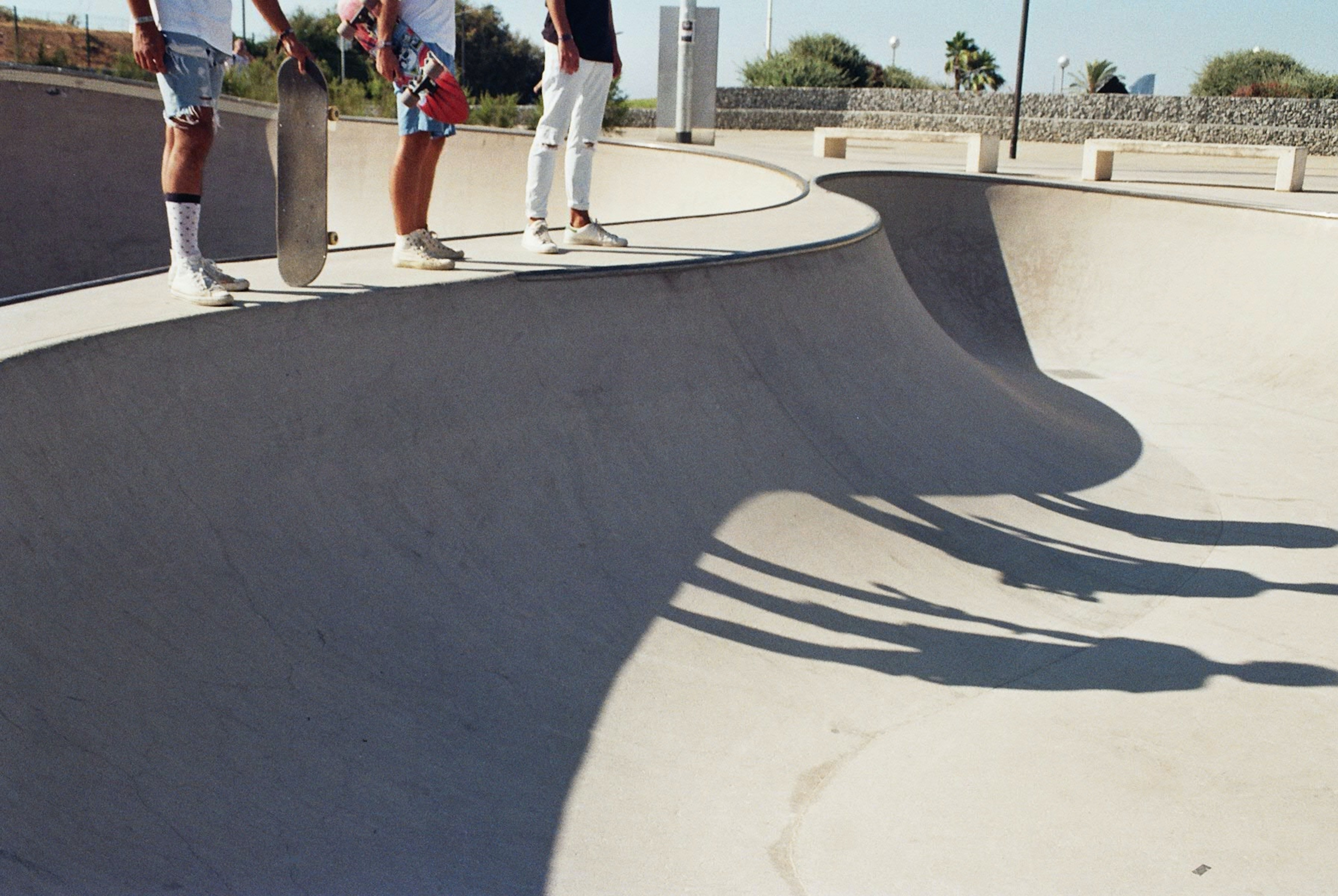 three skaters standing on skateboard concrete ramp with shadow at daytime