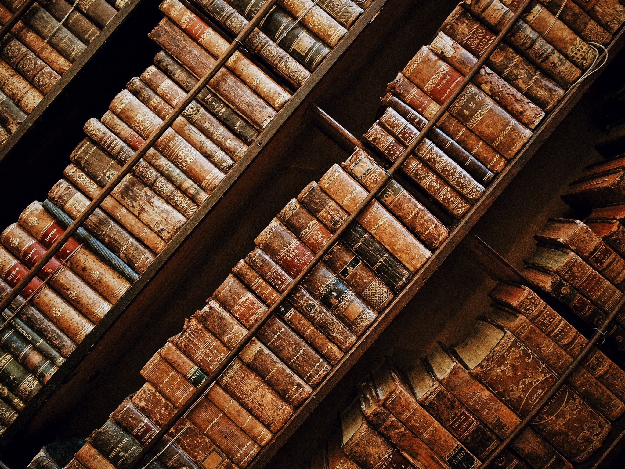 Old antique books in wooden shelves at the library