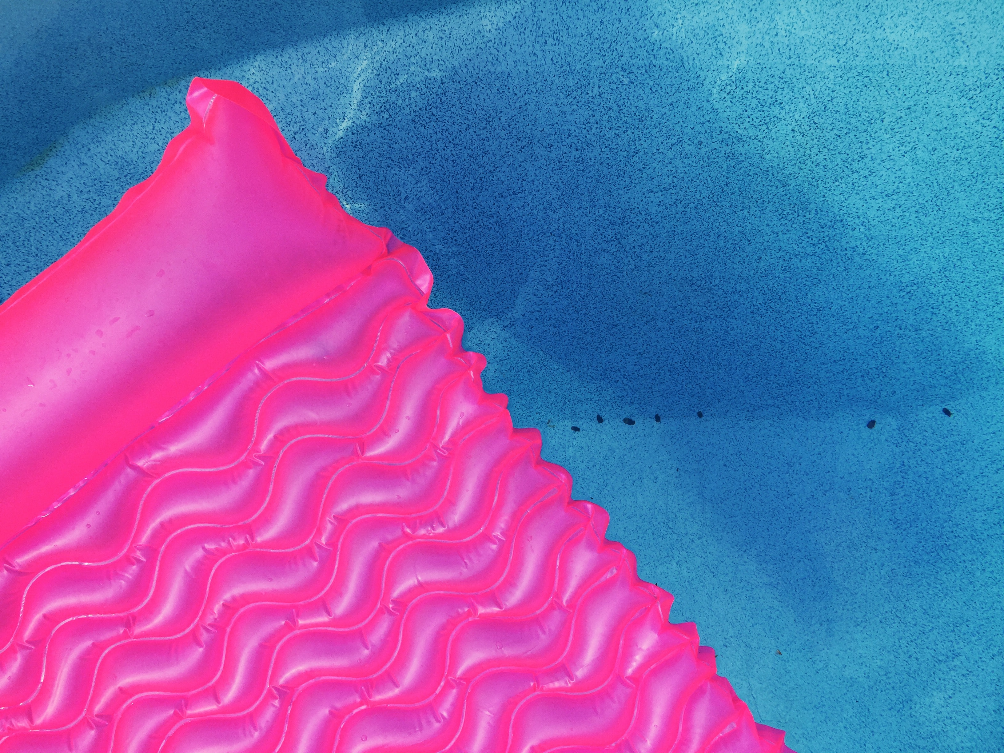 Bright pink pool floaties gliding along blue waters
