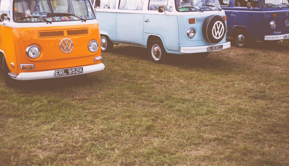 orange Volkswagen vehicles on green grass field
