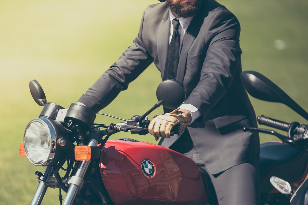 person wearing gray suit jacket riding BMW motorcycle