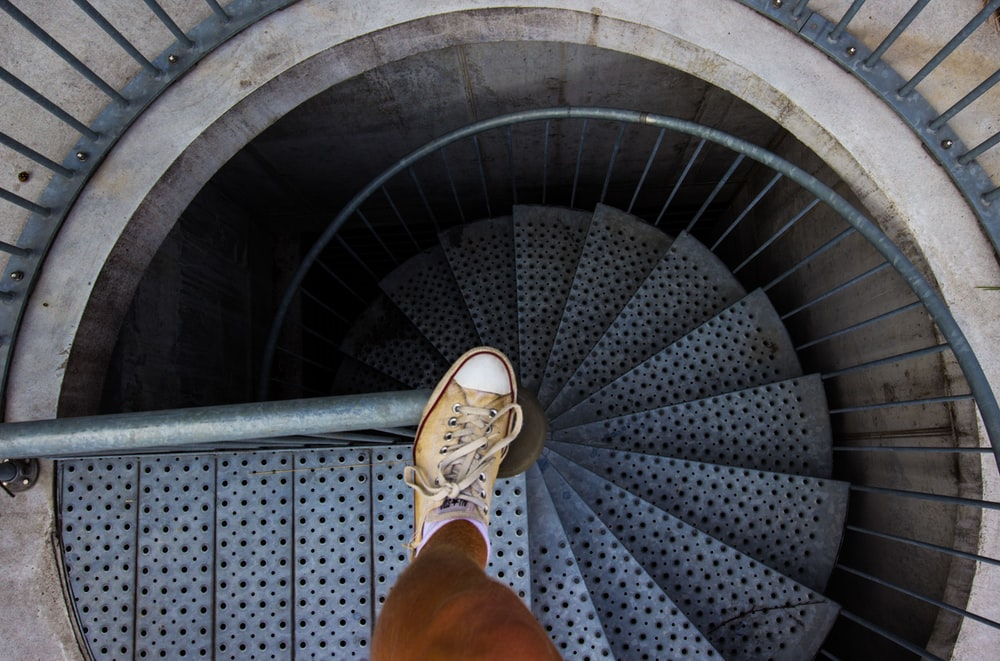 person in brown leather boots standing on spiral staircase