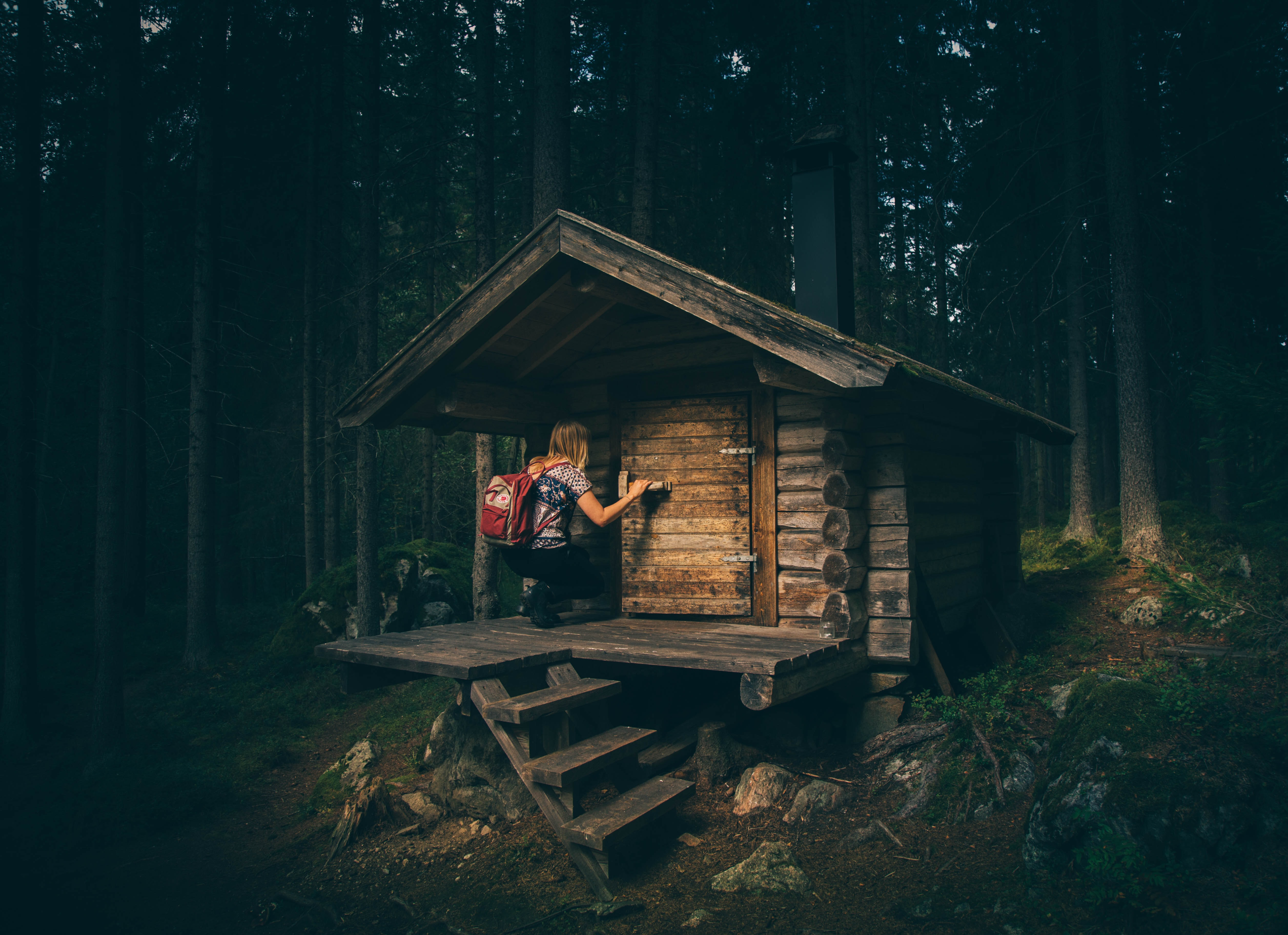 A hiker kneeling on the porch of a small wood cabin in the woods