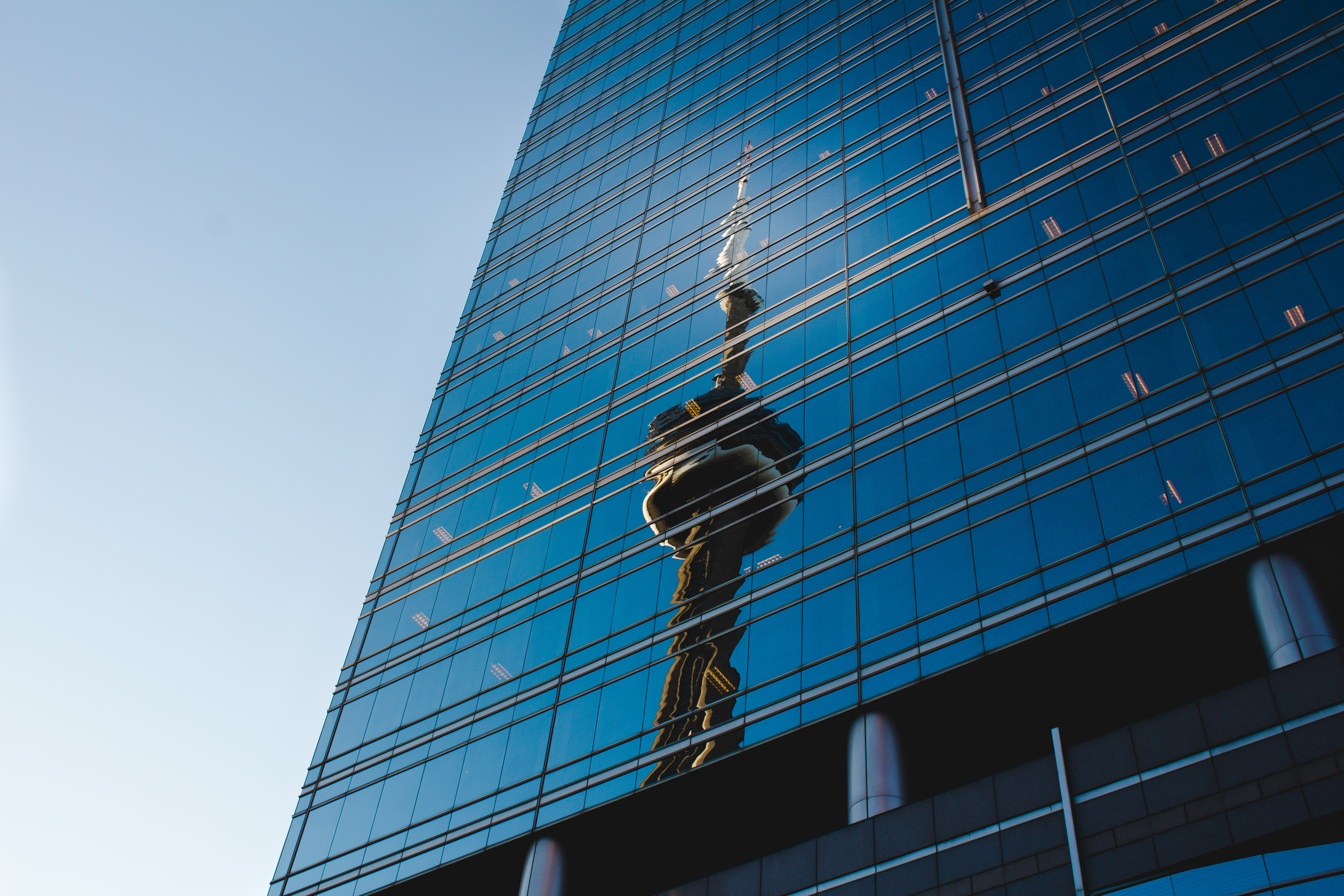 Reflection of CN tower on glass skyscraper windows in daytime, Toronto