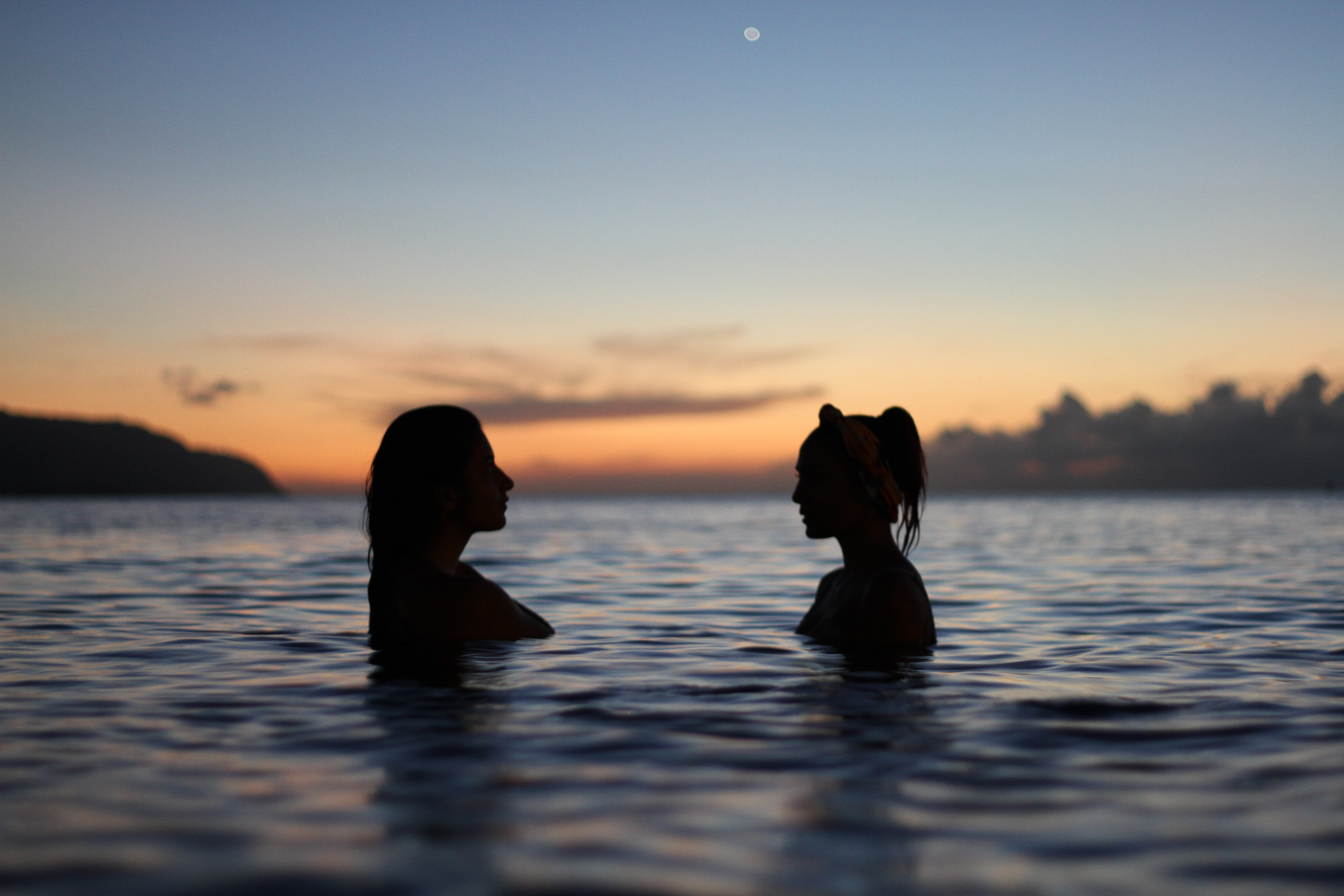 Silhouette of two women facing each other while standing in the waters of sunset Haleiwa beach